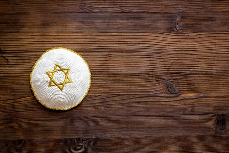 Jewish Kippah Yarmulkes hats with Star of David on wooden table. Religion Judaisim symbol. Top view, space for text