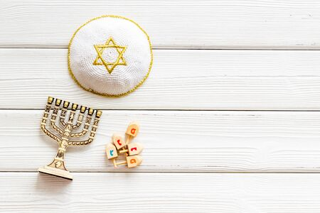 Jewish Kippah Yarmulkes hats with Star of David with menorah. Religion Judaisim symbols on wooden table. Top view, space for text