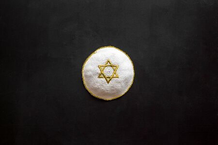 Jewish Kippah Yarmulkes hats with Star of David on black table. Religion Judaisim symbol. Top view, space for text Stock Photo