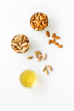 Almond oil - for cooking - in glass bowl near nuts on white background top-down