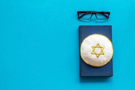 Jewish Kippah Yarmulkes hats with Star of David on Prayer book. Religion Judaisim symbols on blue table. Top view, space for text