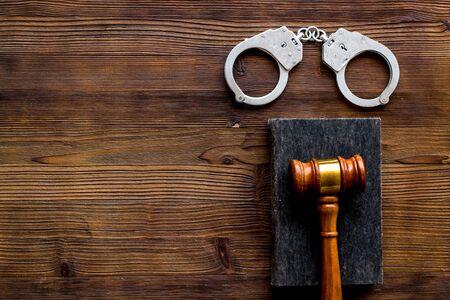 Arrest concept. Handcuffs near judge gavel on dark wooden background top-down copy space Imagens