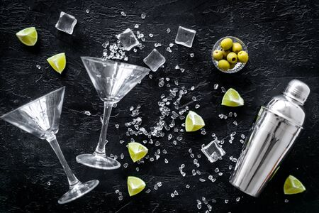 Bar background with martini glasses, shaker, ice, lemon and olives on black table top-down.