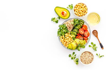 Vegan Buddha bowl. Avocado, quinoa, tomato, spinach and chickpeas vegetables salad on white table top-down. Banque d'images