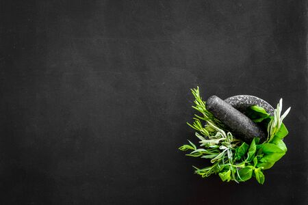 Herbs in ceramic mortar with pestle on black backgroud top-down. Stock Photo
