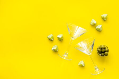 Cocktail concept. Martini glasses near olives and lemon on yellow background top-down.