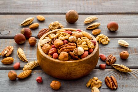 Mixed nuts in bowl - healthy snack - on wooden background.