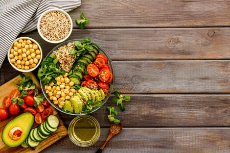 Quinoa, avocado and chickpeas in bowl in hands - balanced healthy food - on wooden table. Top view copy space
