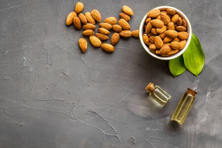 Skin care cosmetics. Almond oil in small bottles on grey background top-down.