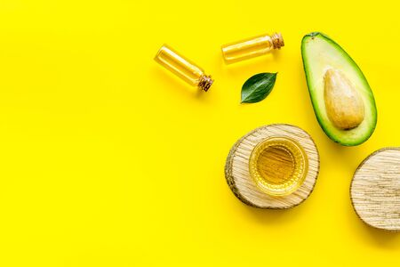 Avocado oil - skin care concept - on yellow background top-down frame copy space