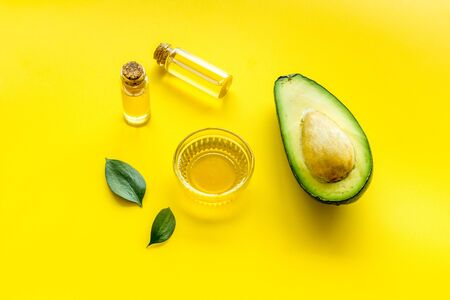 Avocado oil for cosmetology. Sltill lfe with half of fruit and bottles on yellow background.