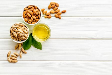 Almond oil - for cooking - in glass bowl near nuts on white wooden background top-down copy space