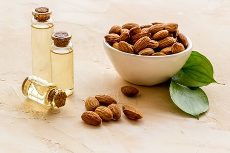 Spa and aromatherapy. Almond oil in small bottles on beige background