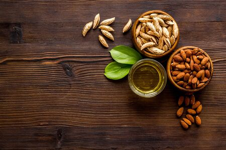 Almond oil - for cooking - in glass bowl near nuts on wooden background top-down copy space