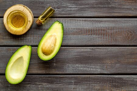 Avocado oil - ingredient for cosmetics - on woode background top-down.