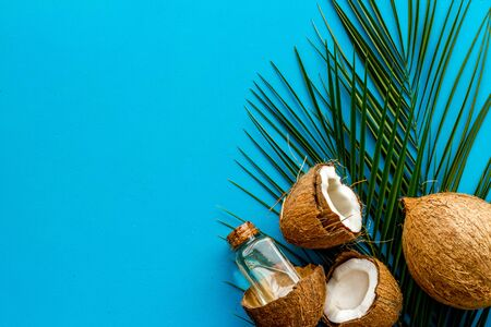 Coconut background with oil on blue background top-down.