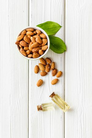 Skin care cosmetics. Almond oil in small bottles on white wooden background top-down.