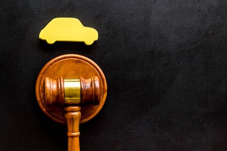 Car credit debt concept with judge gavel on black background top-down.