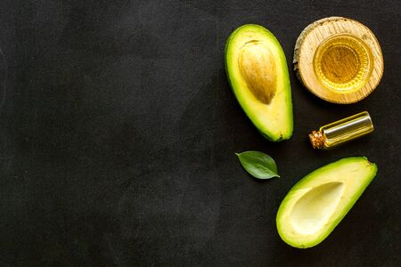 Avocado oil - ingredient for cosmetics - on black background top-down.