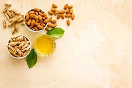 Almond oil - for cooking - in glass bowl near nuts on beige background top-down.