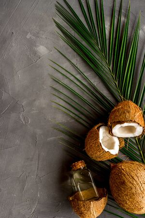 Coconut background with oil on grey background top-down.