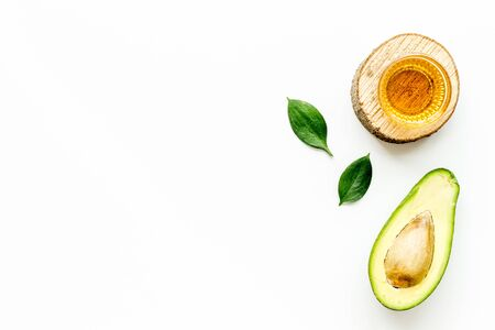 Avocado oil - for cooking - in glass bowl near halfs of vegetable on white background top-down.