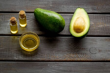 Avocado oil for cosmetology. Sltill lfe with half of fruit and bottles on wooden background.