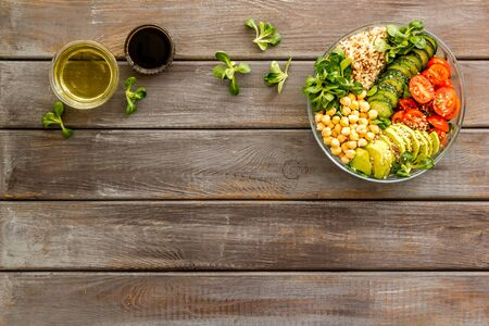 Vegan Buddha bowl. Avocado, quinoa, tomato, spinach and chickpeas vegetables salad on wooden table top-down.