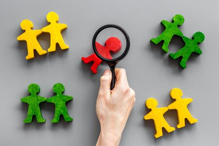 Wooden figures of people under black magnifying glass on gray table. Recruitment, hiring, leadership concept. Top view.