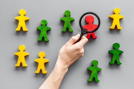 Wooden figures of people under black magnifying glass on gray table. Recruitment, hiring, leadership concept.