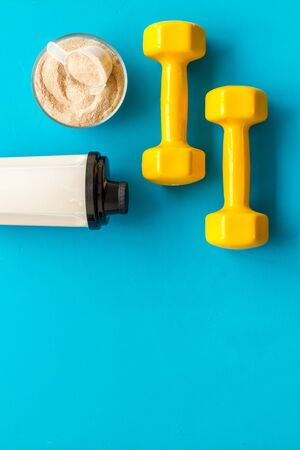 Sport nutrition. Whey protein, shaker, dumbbells on blue background top-down flay lay copy space