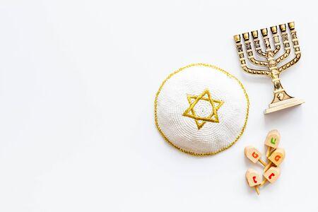 Jewish Kippah Yarmulkes hats with menorah on white table.
