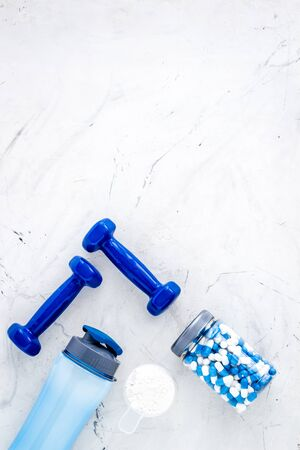 Creatine capsules, protein near shaker and dumbbells - sports supplements - flat lay on white background top view