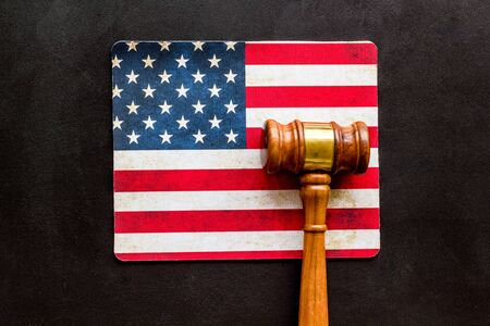 Law and justice in USA concept. Judge gavel near american flag on black background top-down.