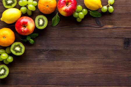 Fresh fruits background with citruses, apple, kiwi and grape on wooden table top-down frame copy space