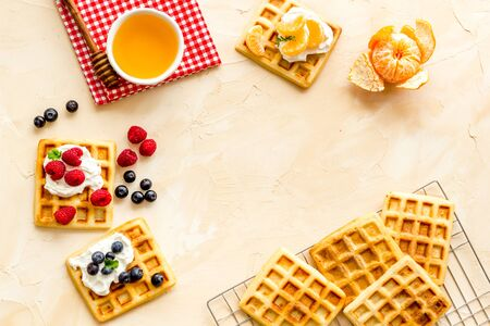 Beautiful yummy snacks. Waffles with cream and friuits on beige background top-down frame copy space