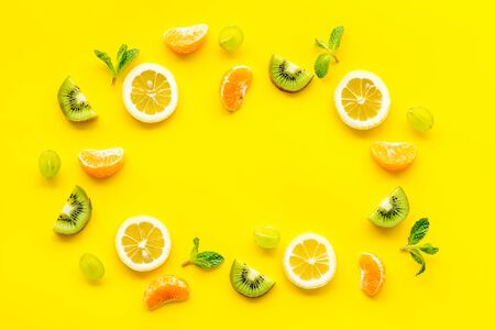 Slices fruites frame. Fruit salad concept with citruses, aplle and kiwi on yellow background top-down copy space