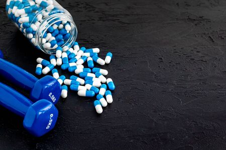 Dumbbells and creatine capsules - sport training concept - on black background copy space