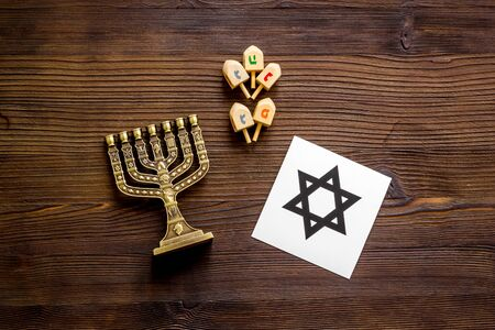 Jewish Kippah Yarmulkes hats, star of David and menorah on wooden table. Top view