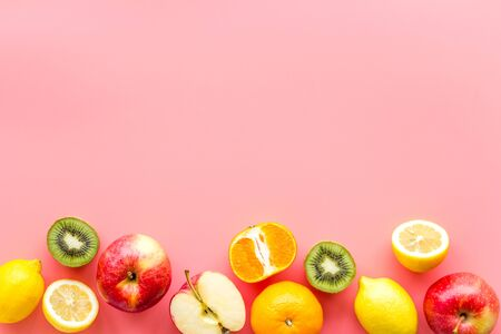Fresh fruits background with citruses, apple, kiwi and grape on pink table top-down frame copy space