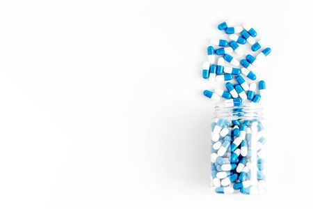 Creatine capsules. Pills scattered on white background top view Stock Photo