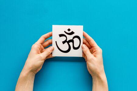 Om - Buddhist inner peace symbol - in hands on blue desk top view Banco de Imagens