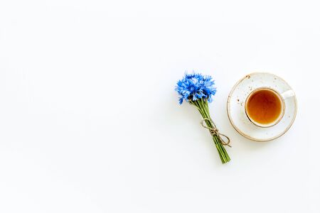 Summer tea party. Cup near cornflowers bouquet on white background top-down.
