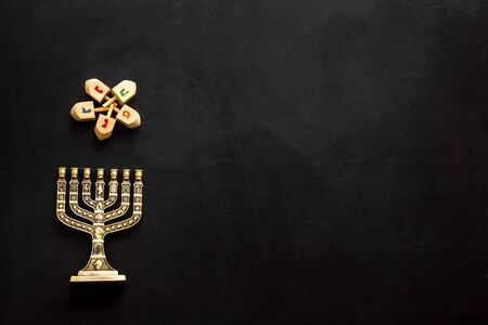 Menorah - traditional Jewish Candelabra - holiday Hanukkah concept on black background, top view, copy space