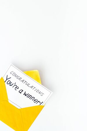 Youre a winner. Envelope with congratulation card on white table top view copy space