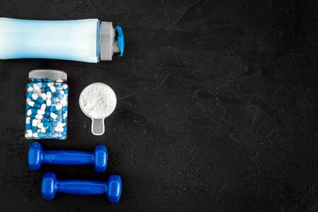 Creatine capsules, protein near shaker and dumbbells - sports supplements - flat lay on black background top view.