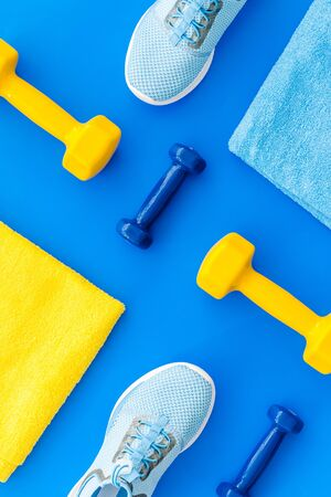 Sport flat-lay with dumbbells, towel, sneakers on blue background top-down.