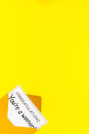 You're a winner. Envelope with congratulation card on yellow table top view.