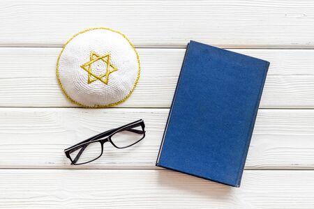 Jewish Kippah Yarmulkes hats with Star of David near Prayer book on white wooden desk top view Stock Photo
