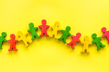 Teamwork, teambuilding concept. Wooden figures of people on yellow background top view.